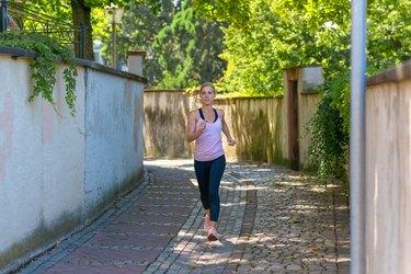 Fit woman jogging down a leafy shady lane