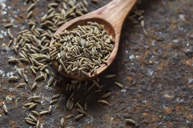 Close view of a wooden spoon full of cumin seeds as a spice for weight loss