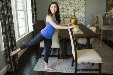 Woman doing a barre workout with a chair in her dining room