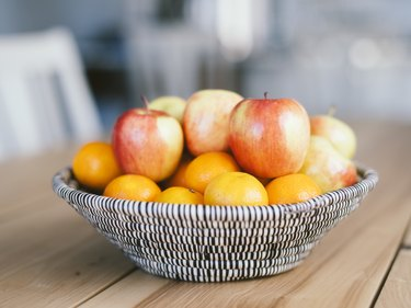 Fruit basket of apples and oranges on a wooden table