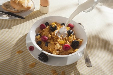 Milk being poured on a bowl of cornflakes with fruit