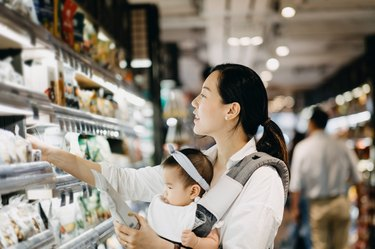 Beautiful Asian woman carrying cute baby girl shopping for organic green marketing products in grocery store