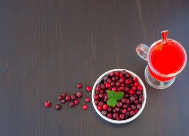 Glass of cranberry juice and a bowl of cranberries