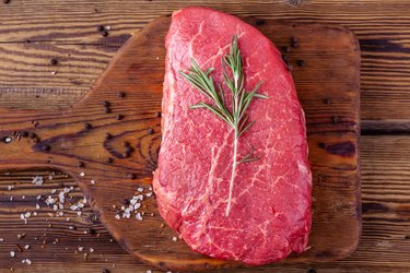 Raw Fresh Steak Served with Rosemary and Scattered Herbs on Rustic Wooden Board