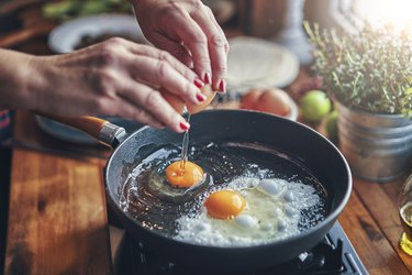 close view of a woman frying eggs to eat, as a natural remedy for headaches