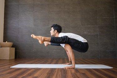 Yogi doing firefly yoga pose at home