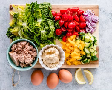 Egg and tuna salad ingredients on a chopping board