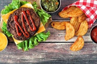 Picnic scene with hamburger and potato wedges over dark wood