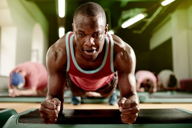 Front view of a sweaty man holding a plank position in a workout class