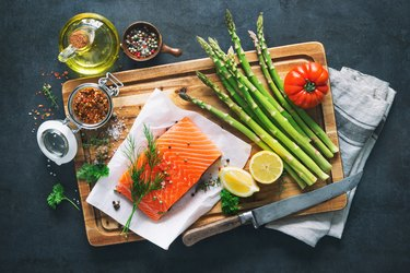 Fresh salmon fillet fish recipes with aromatic herbs, spices and vegetables