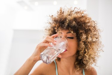 Thirsty African American woman drinking water.