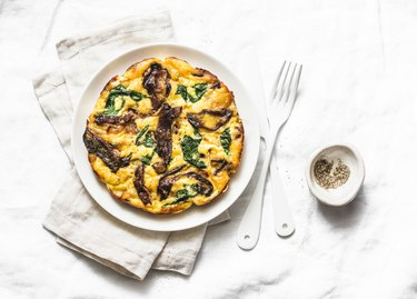 Porcini mushrooms, potatoes, spinach baked frittata - delicious breakfast, snack, tapas on a light background, top view