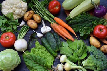 Composition on a dark background of organic vegetarian products: green leafy vegetables, carrots, zucchini, potatoes, onions, garlic, tomatoes. Top view