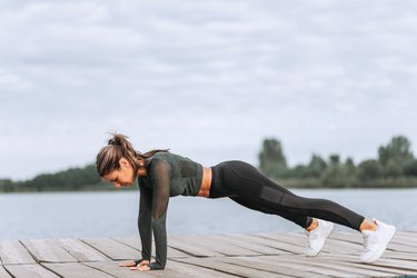 Side view of fit woman exercising on wooden river boardwalk.