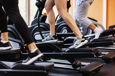 people working out on an elliptical trainer in gym.
