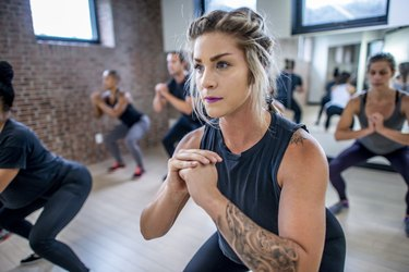 Diverse fitness class doing squats