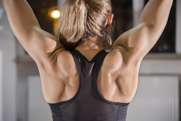 Photo of Athletic young woman showing muscles of the back