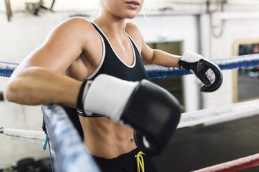 Female boxer resting in boxing ring
