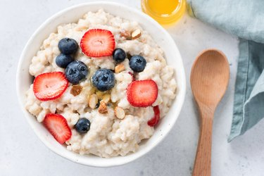 Oatmeal porridge with berries and almonds in bowl, top view