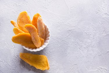 Dehydrated and dried mango chips in white bowl. Close up.