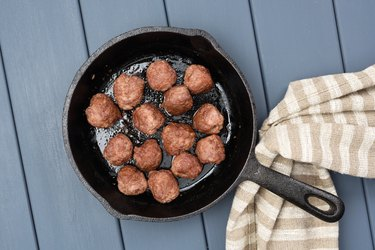 Homemade beef meatballs fried in cast iron pan with flax cloth on gray wooden table