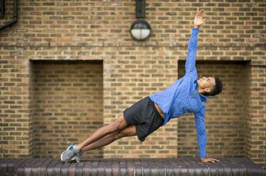 man doing side plank in front of brick wall as part of full-body workout