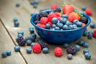 Mixed Organic Berries in a bowl on a wooden table