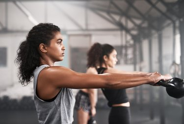 Women doing kettlebell swings, a high-intensity exercise that can aid weight loss