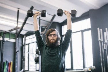 Man doing a shoulder press with dumbbells at the gym