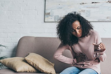 unhappy african american woman holding glass of water while sitting on sofa and suffering from stomach pain