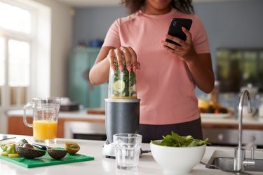 Close Up Of Woman Using Fitness Tracker To Count Calories For Post Workout Juice Drink She Is Making
