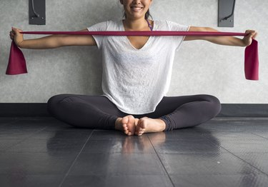 Smiling Young Active Female using a theraband exercise band to strengthen her arms muscles in the studio