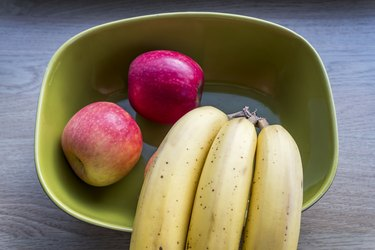 Fresh apples and bananas on green bowl