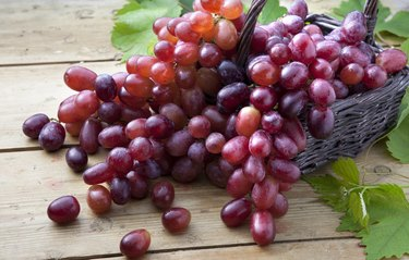 Red grapes in braided basket on wooden table