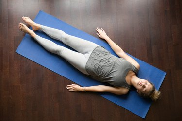 A woman lying on a yoga mat with her eyes closed, practicing body scan meditation