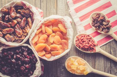 Dried fruits in paper bag on wooden table
