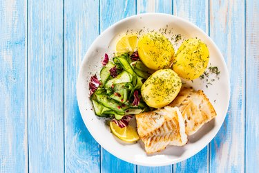 Fried cod fillet with boiled potatoes and vegetables