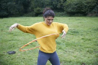 Woman hula hooping in field