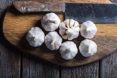 Garlic on wooden chopping board.