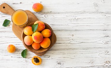 Ripe apricots and glass of juice in wooden bowl