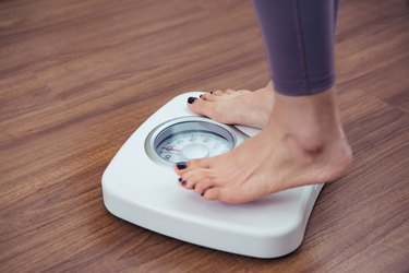 A woman stepping onto a white bathroom scale to weigh herself