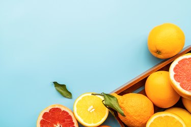 Various citrus fruit on blue background top view with copy space