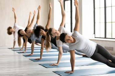 Diverse young people doing Side Plank exercise, practicing yoga