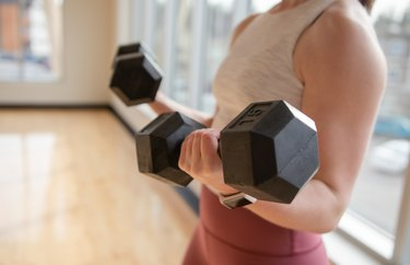 Low Section Of Woman Exercising With Dumbbells At Home