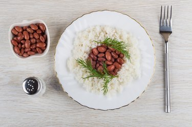 Red beans with rice in plate, salt, fork on table