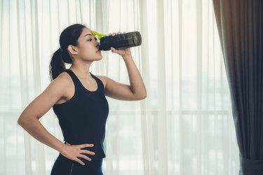 A woman holding a bottle of protein supplements on muscle drink to strengthen health care to vigorous and beautiful.