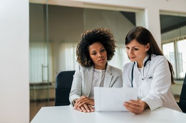 Portrait of a beautiful female doctor and patient looking at cholesterol test results.