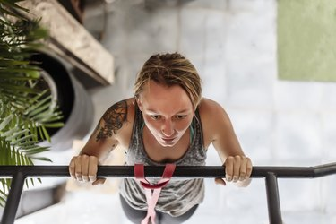 High angle view of woman doing pull-ups at gym