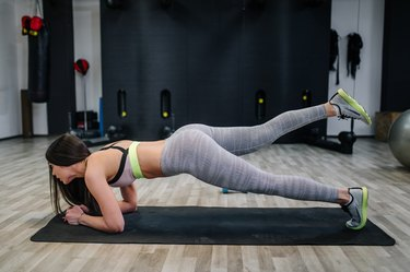 Young woman doing a plank on a exercise mat