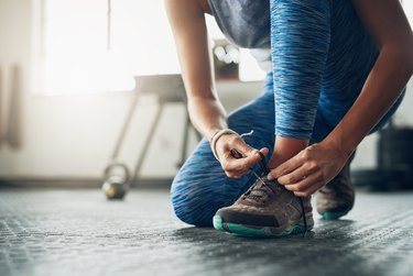 A woman tying her sneakers before a workout